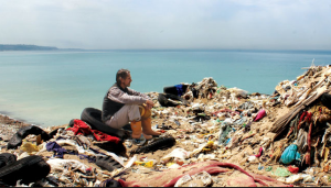 Jeremy Irons sits amid a pile of trash